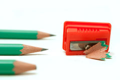 Pencil. Two dull green pencil and one sharp and sharpener on a white background royalty free stock photo