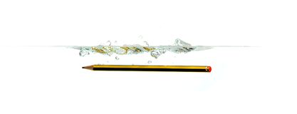 Pencil on water. Pencil falling in the water and creating waves Royalty Free Stock Images