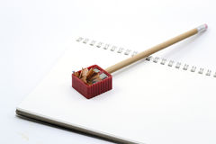 Pencil on white notebook, sharpener and pencil shavings Royalty Free Stock Photography