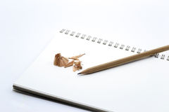 Pencil on white notebook, sharpener and pencil shavings Stock Photography