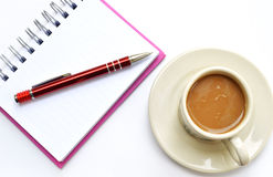 Pencil on a white spiral squared notebook with cup of coffee. Pen on a white spiral squared notebook with cup of coffee viewed from above Stock Photos