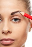 Pencil woman's eyebrows with a carpenters pen stock images