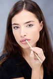 Pencil on woman's lips. Woman applying cosmetic pencil on lips Royalty Free Stock Images