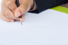 Pencil in women hand writing on paper. Stock Photo