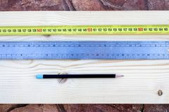 Pencil, rule and a meter on a wooden background royalty free stock images