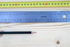 Pencil, rule and a meter on a wooden background royalty free stock image