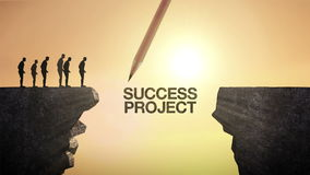Pencil write `SUCCESS PROJECT`, connecting the cliff. Businessman crossing the cliff, business concept.