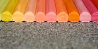 Pencile da cera alinhou, fundo colorido com as varas multicoloridos na cor pastel fotos de stock royalty free