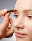 Penciling eyebrow for young girl Stock Images