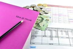 Pencill, dinero, cuaderno rosado y calculadora colocados en el documento Imagen de archivo