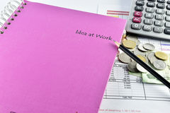 Pencill, money,  pink notebook and calculator placed on document Royalty Free Stock Photography