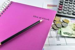 Pencill, pengar, rosa anteckningsbok och räknemaskin som förläggas på dokument Arkivfoton