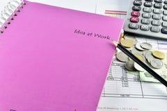 Pencill, pengar, rosa anteckningsbok och räknemaskin som förläggas på dokument Royaltyfri Fotografi