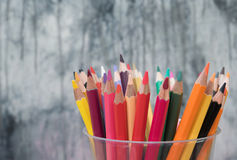 Pencills. Pens and pencils in a glass in front of wall background Stock Photo