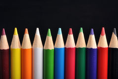 Pencils. Row of color pencils on black background Royalty Free Stock Photo