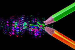 Pencils background. Orange and green neon colored smashed pencils Stock Photography