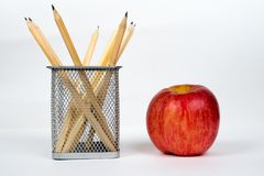 Pencils in basket with apple on white Royalty Free Stock Photo