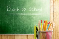 Pencils in basket container with green stapler with chalkboard background. Back to School concept stock photos