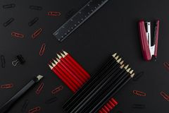 Pencils in black and red, stapler, red and black clips, ruler and knife  on a black background. The stationery in red and black: pencils and a stapler, a ruler stock photo