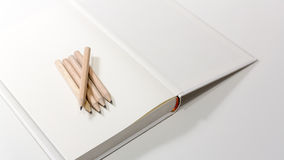 Pencils on a blank note book Royalty Free Stock Photos