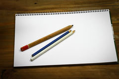 Pencils on blank white paper. On wooden table Royalty Free Stock Photos