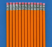 Pencils on blue. Multiple pencils in a row eraser end up, isolated against a blue background Stock Image