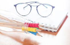 Pencils in bottle with eyeglasses on notebook Stock Photos