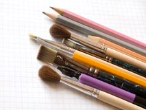 Pencils and brushes on copy-book Stock Photography