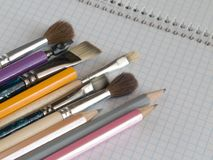 Pencils and brushes on copy-book Stock Photos