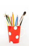 Pencils and brushes in a cup. Colored pencils and brushes in a red dotted cap on white background stock photography