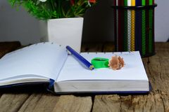 Pencils case , blue pencil ,opened notebook. And green pencil sharpener on wood table with flowers in vase stock images