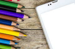 Pencils color and smart phone on wood background, top view Royalty Free Stock Images