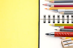 Pencils of different colors and spiral notepad on yellow backgro Royalty Free Stock Photography