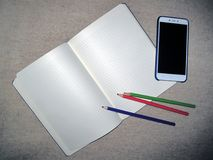 Pencils for drawing in a notebook. Write a congratulatory text in a notebook in colorful pencils Stock Photos