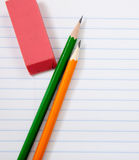 Pencils and an eraser on notebook paper Stock Photos