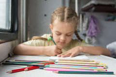 Pencils in the foreground, in the background a six year old girl drawing pencils in a second-class train carriage Stock Photos