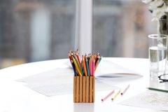 Pencils in holder with coloring pictures for adults. On table Royalty Free Stock Image