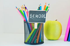 Pencils in holder, yellow appleand book Royalty Free Stock Photo