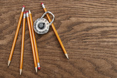Pencils and lock on wood surface Stock Images