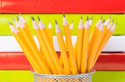 Pencils in a metal Cup in the background. colorful books. stock image