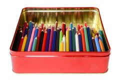 Color pencils in a tin box. Pencils of multiple colors inside a red tin box with reflective sides Royalty Free Stock Image