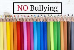 Pencils with No Bullying text. Colorful pencils on white wooden background with No Bullying sign Stock Image