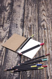 Pencils and a notebook. Black colored pencils and a notebook on a wooden background Stock Photos