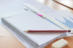 Pencils, notebooks and chart in office. Pencils, notebooks and chart on desk in office Royalty Free Stock Image
