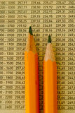 Pencils and numbers. Close up of two pencils on a background of numbers Royalty Free Stock Image