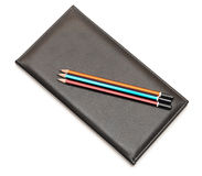 Pencils over note book Stock Photos