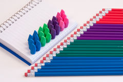 Pencils, Pad & Erasers. Colorful pencils, erasers and a small notepad Royalty Free Stock Photography