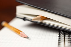 Pencils on the pages of an closed notebook for records Stock Image