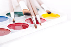 Pencils, paints and brushes on a white Stock Images