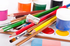Pencils, paints and brushes on a white Royalty Free Stock Photography